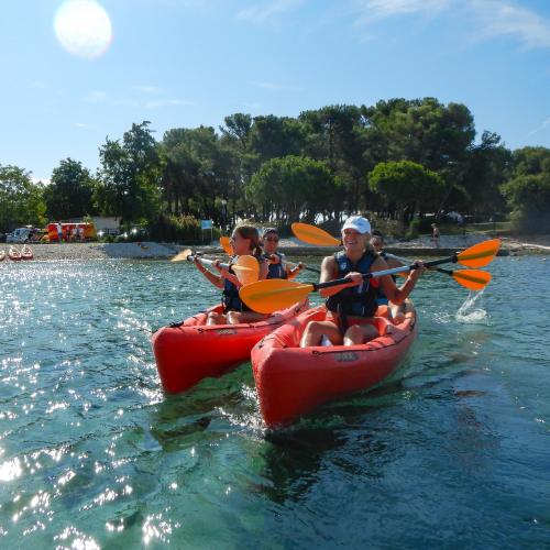 people paddling red kayaks on ocean